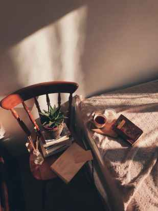 An old chair stacked with books and a plant sits next to a bed, with tea and a candle.